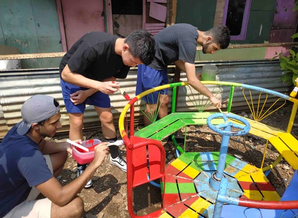Volunteers painting the playground